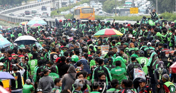Massa ojek online menggelar aksi di depan Gedung DPR, Jakarta, Jumat (28/2). Mereka menuntut pernyataan pimpinan Komisi V DPR Nurhayati Monoarfa terkait pernyataan soal pembatasan motor. Foto: Ricardo - JPNN.com