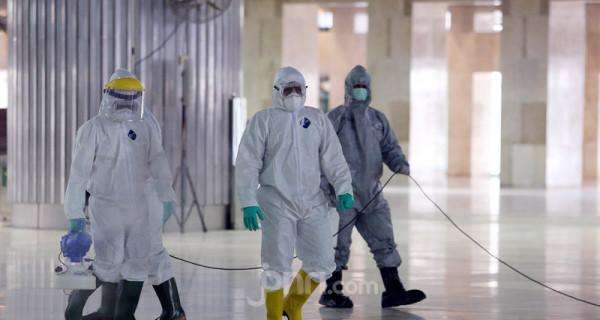 Petugas melakukan sterilisasi dengan cairan disinfektan di Masjid Istiqlal, Jakarta, Jumat (13/3). Sterilisasi dengan disinfektan dalam rangka pencegahan virus corona atau Covid-19. Foto: Ricardo - JPNN.com