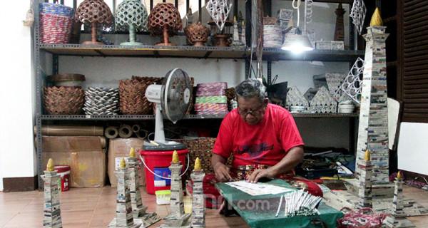 Sugito (68) menyelesaikan pembuatan kerajinan berupa miniatur Monas di Bank Sampah Tri Alam Lestari, Pesanggrahan, Jakarta, Minggu (13/6). Hasil kerajinan yang memanfaatkan limbah kertas koran bekas dari bank sampah tersebut dijual dengan harga antara Rp 50.000 hingga Rp 250.000. Foto: Ricardo - JPNN.com