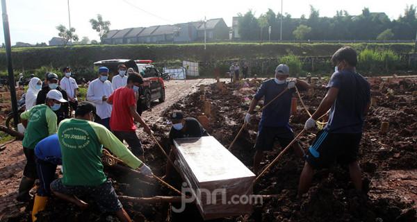 Petugas pemakaman di TPU Jombang, Tangerang Selatan (Tangsel), Banten, tengah memakamkan jenazah korban Covid-19, Senin (21/6). Angka kematian akibat Covid-19 di Tangsel pascalibur Lebaran meningkat rata-rata 20 persen. Dalam sehari terdapat 5-10 jenazah korban Covid-19 yang dimakamkan di TPU tersebut. Foto: Ricardo - JPNN.com