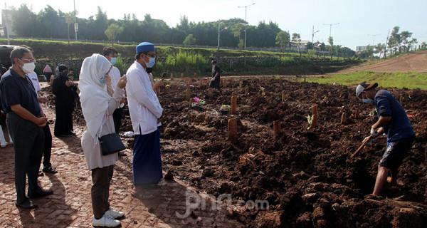 Keluarga korban Covid-19 berdoa pada proses pemakaman jenazah di TPU Jombang, Tangerang Selatan (Tangsel), Banten, Senin (21/6). Angka kematian akibat Covid-19 di Tangsel pascalibur Lebaran meningkat rata-rata 20 persen. Dalam sehari terdapat 5-10 jenazah korban Covid-19 yang dimakamkan di TPU tersebut. Foto: Ricardo - JPNN.com