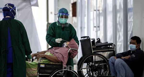 Petugas medis melakukan penanganan kepada warga yang diduga terpapar virus Covid-19 di RSUD Cengkareng, Jakarta, Kamis (24/6). Lonjakan kasus Covid-19 berdampak pada tak terbendungnya pasien yang berdatangan ke rumah sakit. Foto: Ricardo - JPNN.com