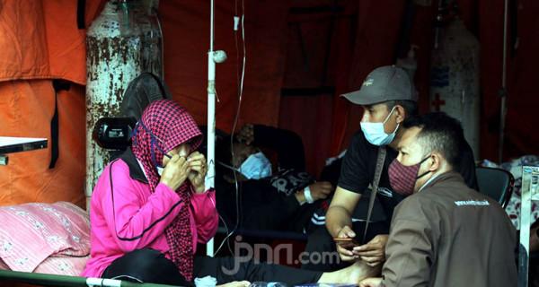 Pasien Covid-19 di RSUD Bekasi, Jawa Barat, Sabtu (26/6), saat mendapat perawatan di tenda darurat milik BNPB. Penumpukan pasien Covid-19 di RSUD Bekasi sempat terjadi lonjakan pada Jumat, (25/6/2021). Foto: Ricardo - JPNN.com