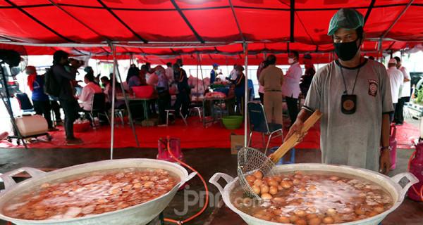 Pekerja mengolah bahan baku masakan di dapur umum Tagana di halaman Gedung Kemenso, Jakarta, Senin (28/6). Kemensos menyiapkan makanan siap saji untuk dibagikan kepada warga dan tenaga kesehatan yang terdampak Covid-19. Foto: Ricardo - JPNN.com
