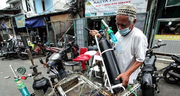 Warga melakukan pengisian ulang tabung oksigen di kawasan Manggarai, Jakarta, Rabu (30/6). Permintaan tabung oksigen baru dan pengisian tabung oksigen mengalami peningkatan drastis menyusul lonjakan kasus Covid-19 di DKI Jakarta. Foto: Ricardo - JPNN.com