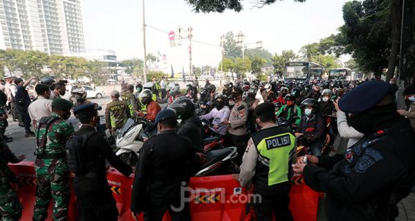 Petugas gabungan dari TNI dan Polri memutarbalik kendaraan yang melintas di pos penyekatan pembatasan menuju Jakarta di kawasan Kalideres, Jakarta, Senin (5/7). Polisi melakukan penyekatan di 63 titik wilayah di Jadetabek saat Pemberlakuan Pembatasan Kegiatan Masyarakat (PPKM) Darurat yang berlangsung hingga 20 Juli 2021. Foto: Ricardo - JPNN.com