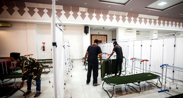Petugas menyiapkan velbed untuk tempat tidur pasien Covid-19 di GOR Matraman, Jakarta, Jumat (16/7). GOR Matraman siap difungsikan menjadi tempat isolasi bagi pasien Covid-19 berstatus orang tanpa gejala (OTG) dan bergejala ringan. Foto: Ricardo - JPNN.com