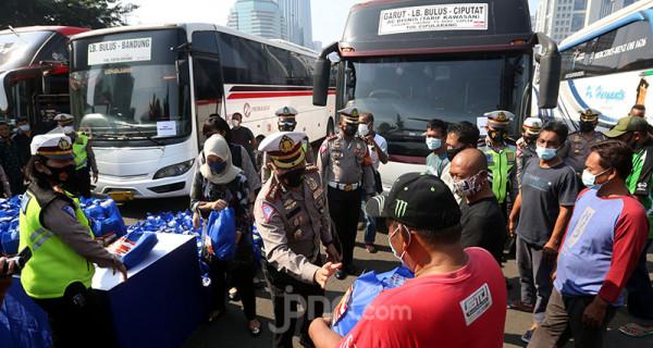 Dirlantas Polda Metro Jaya Kombes Sambodo Purnomo Yogo memberikan paket bantuan kepada para sopir bus umum di Mapolda Metro Jaya, Sabtu (17/7). Polisi menjaring 36 bus yang kedapatan melanggar ketentuan PPKM Darurat. Foto: Ricardo - JPNN.com